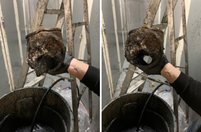 Hand holding clogged pipe before cleaning